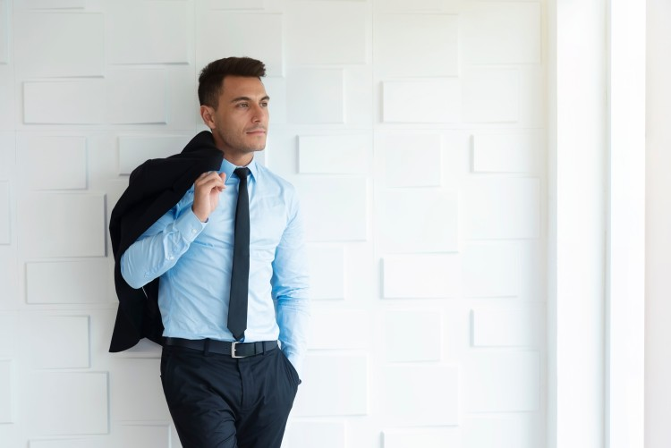 portrait of smart business man in suit standing at white wall in office t20 1b3nxw